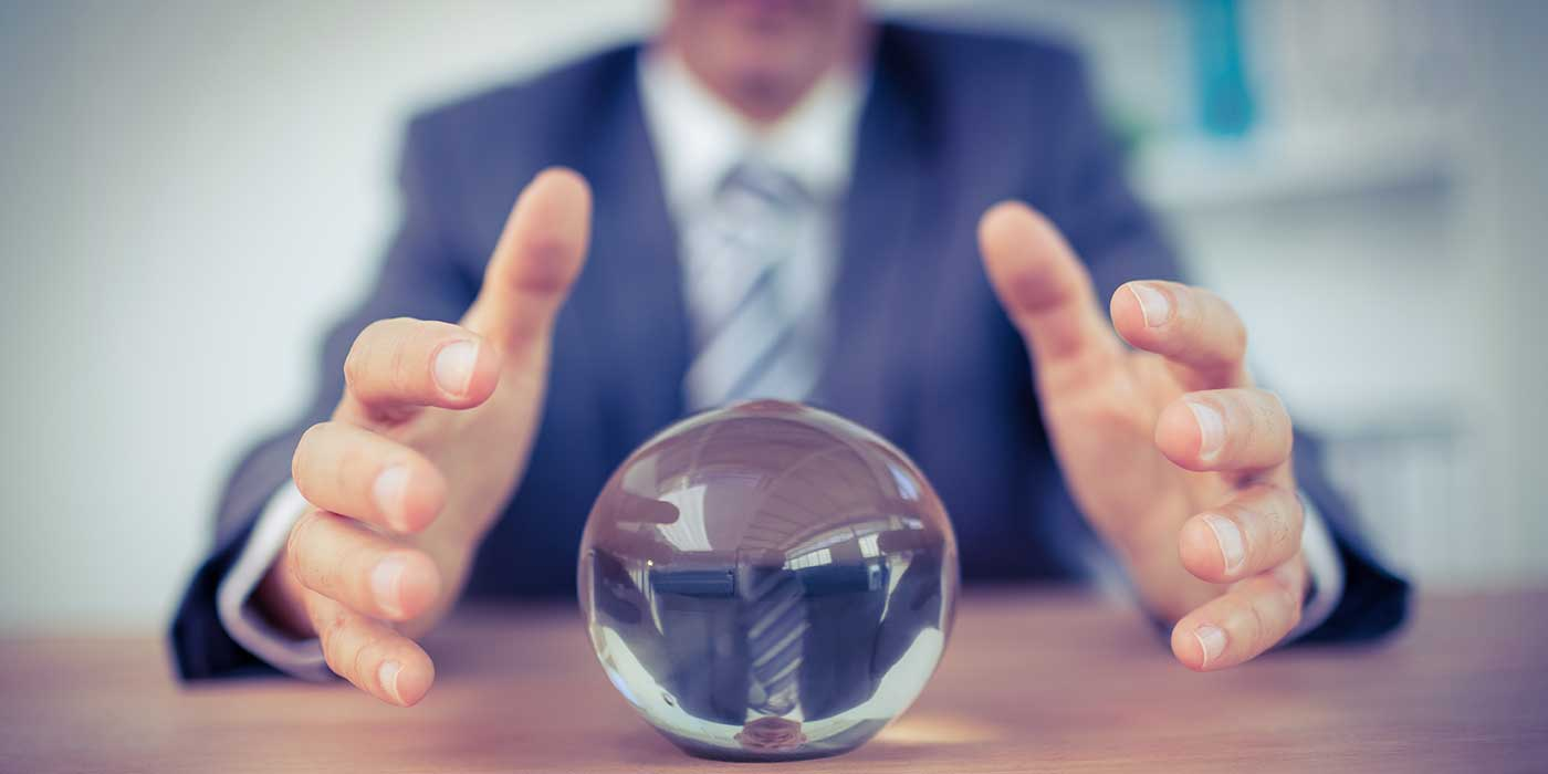 businessman making predictions from crystal ball